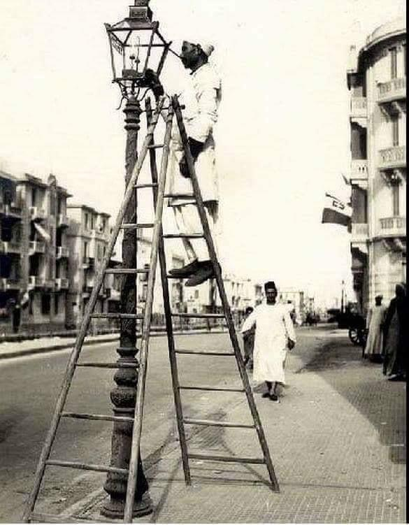 المشعَلجي يُنير أعمِدة الإنَارهـ فِي احد الشَوارع الرَئيسيهـ بِالاسڪَندرية عَام ١٩١٠